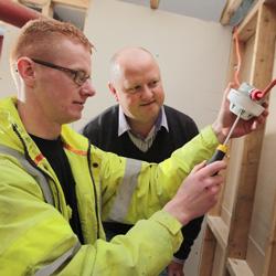 A trainee fixes electrics