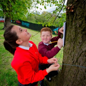Mary Patricia Craig and Kiane Dickson from Holy Family and Currie Primary School meet at the peace wall gate in Alexandra Park to record the girth of a tree during a Forest School programme shared by the two interface schools.