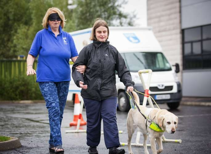 Torie Tennant leads Guide Dogs Volunteer Ann Carnachan blindfolded through an obstacle course.