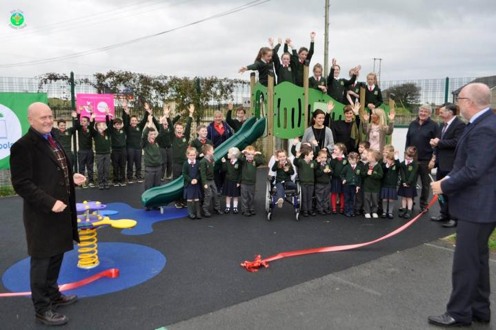Professor Peter Finn and Mr Ed Cousins cutting the ribbon, along with Mr Robert Dinsmore Principal of Holy Cross Primary School Atticall and teachers and staff with some of the Board of Governors.